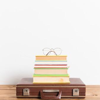 Klassische brillen auf stapel büchern auf weinlesekoffer