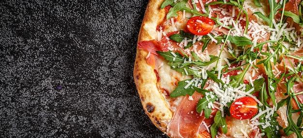Klassische dünne pizza mit großen seiten, schinken, kirschtomaten, rucola, parmesan