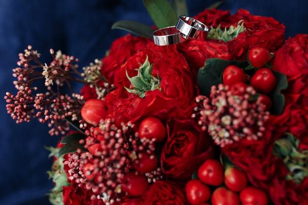 Klassische eheringe aus weißgold auf rotem blumenstrauß