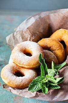Klassische frische donuts mit zuckerglasur und lavendelblüten und minzblättern