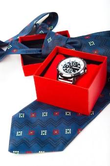 Klassische geschäftsuhren in roter box und abstrakter blauer krawatte