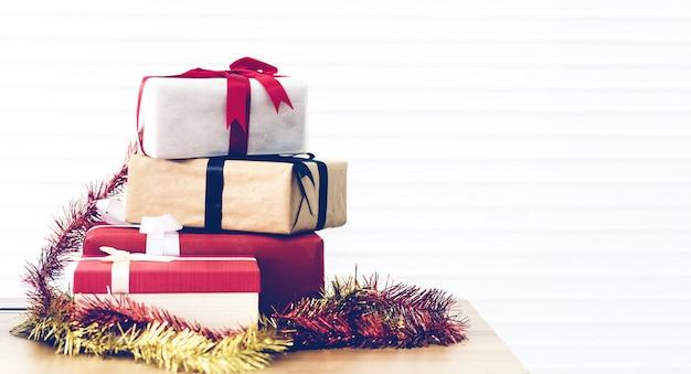 Klassische geschenkboxen des weihnachtsneuen jahres, die mit papier auf holztisch einwickeln