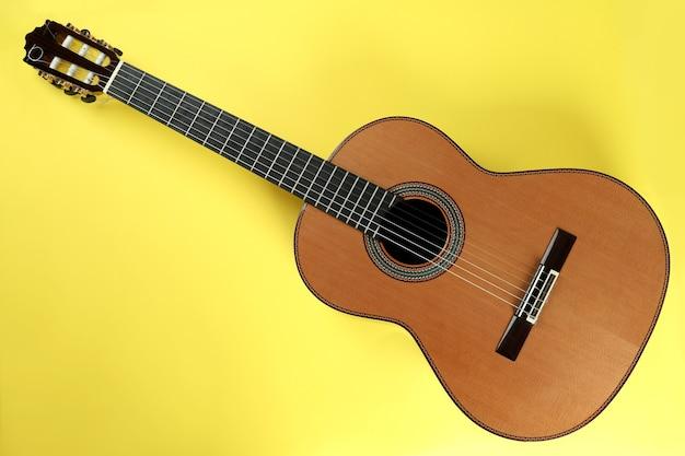 Klassische gitarre auf gelbem hintergrund, ansicht von oben
