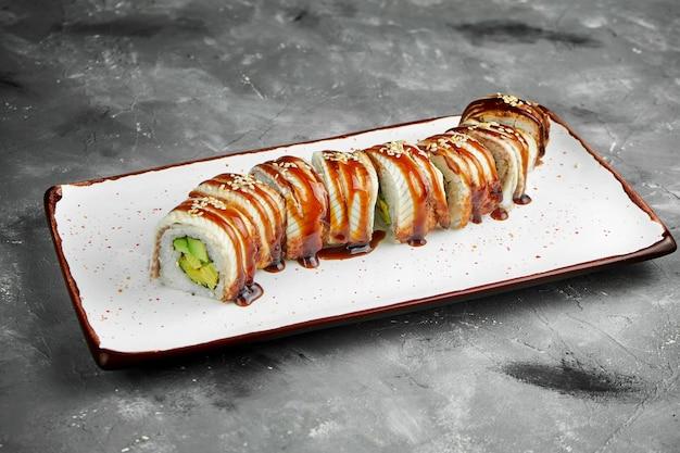 Klassische goldene drachensushi-rolle mit avocado-, aal-, omelett- und unagi-sauce auf einem weißen teller auf einem grauen tisch. selektiver fokus, rauschkorn am pfosten