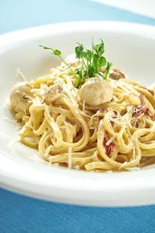 Klassische, hausgemachte italienische pasta (spaghetti) in käsesauce mit putenfleischbällchen und sonnengetrockneten tomaten in einem weißen teller auf blauer tischdecke