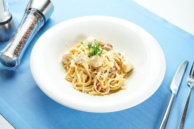 Klassische, hausgemachte italienische pasta (spaghetti) in käsesauce mit putenfleischbällchen und sonnengetrockneten tomaten in einem weißen teller auf einer blauen tischdecke