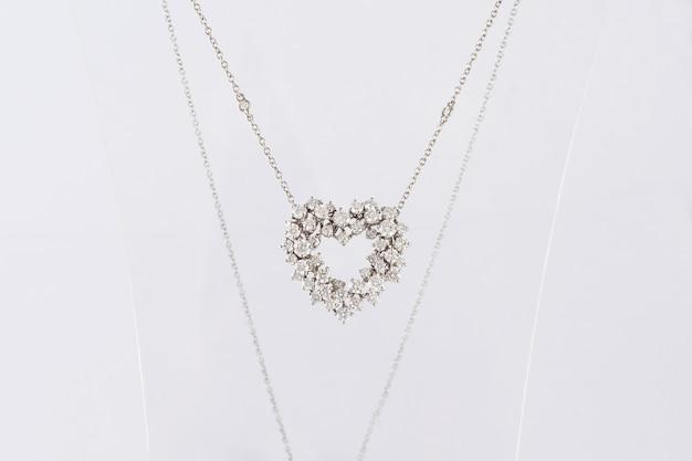 Klassische herzförmige diamantanhänger-halskette auf transparentem ständer