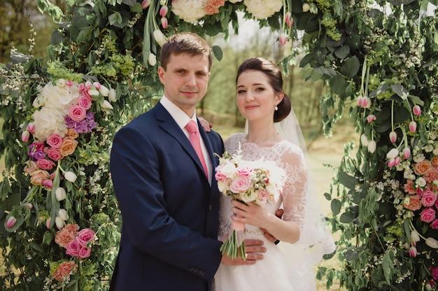 Klassische hochzeit im frühjahr. die braut und der bräutigam auf dem hintergrund eines bogens mit frischen blumen. zeremonie im freien.