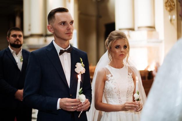 Klassische hochzeitszeremonie der stilvollen jungen luxusbraut und des bräutigams in der alten kirche