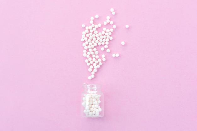 Klassische homöopathiekügelchen in den weinleseglasflaschen auf rosa