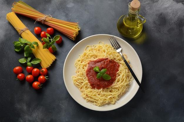 Klassische italienische spaghetti-nudeln mit tomatensauce und basilikum auf teller