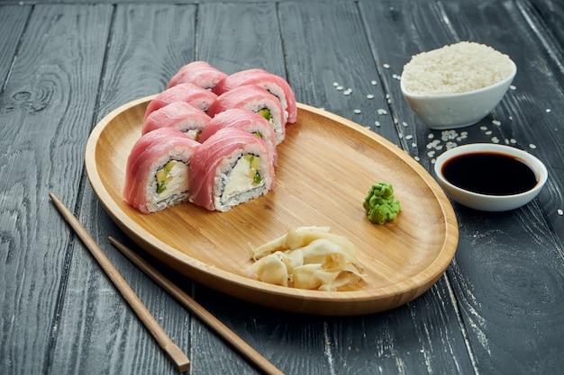 Klassische japanische sushi-rollen - philadelphia-rollen mit frischkäse, gurke und thunfisch auf einem bambusteller auf einem schwarzen hölzernen hintergrund