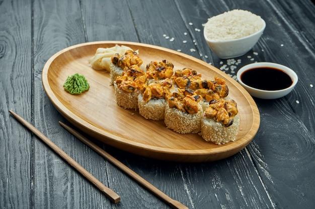 Klassische japanische sushirollen - gebackene brötchen mit frischkäse, würziger sauce und muscheln auf einem bambusteller auf einem schwarzen hölzernen hintergrund