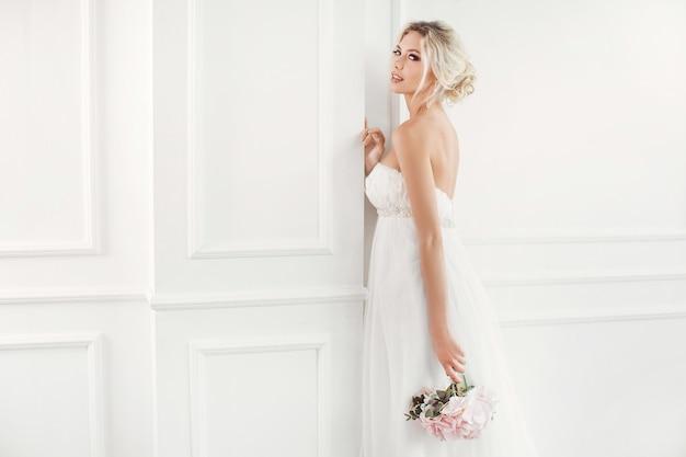 Klassische junge gourgeous braut. studio-innenmode-aufnahme des modemodells im hochzeitskleid mit blumenstrauß im weißen raum.