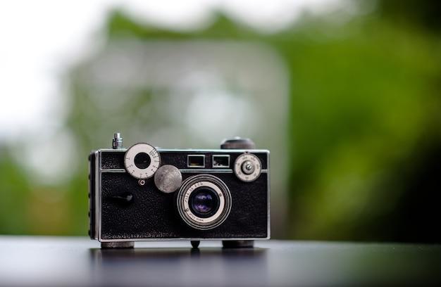 Klassische kamera auf den tisch gelegt sieht nicht teuer aus. fotografie-ideen und alte kamerapflege