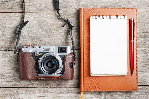 Klassische kamera mit leerer notizblockseite und rotem stift auf grauem hölzernem, weinleseschreibtisch mit telefon.