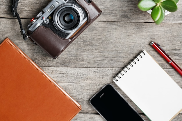 Klassische kamera mit leerer notizblockseite und rotem stift auf grauer hölzerner, weinlesetabelle mit telefon und grüner blume. braunes notizbuch.