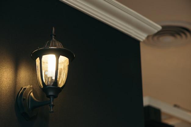 Klassische lampe auf schwarzer wand.
