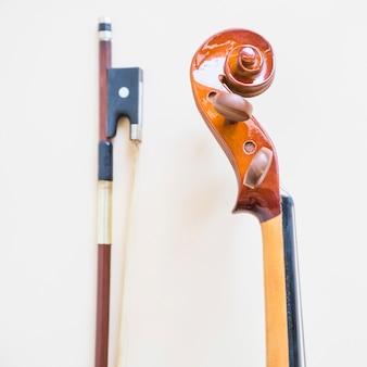 Klassische musikalische violine und bogen gegen weißen hintergrund