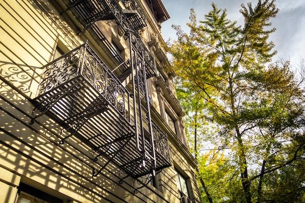 Klassische new yorker fassade mit treppe und buntem baum in der herbstsaison