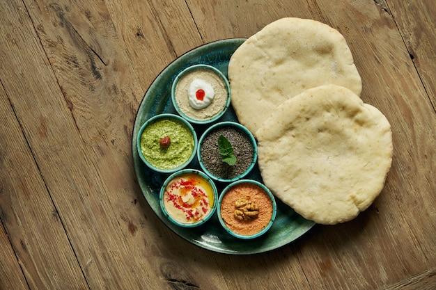 Klassische östliche snacks mit pita-meze. in eine kleine schüssel geben - hummus, paprikapaste, oft mit walnüssen, joghurt, auberginenpaste.