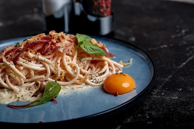 Klassische pasta carbonara mit eigelb auf einem teller. nudeln auf einem blauen teller auf einer dunklen oberfläche ausgelegt. konzept der italienischen küche, schöne serviergerichte, nahaufnahme.