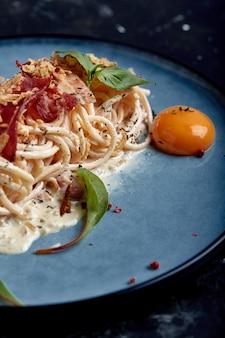 Klassische pasta carbonara mit eigelb auf einem teller. nudeln auf einem blauen teller in einer dunkelheit ausgelegt. konzept der italienischen küche, schöne serviergerichte, nahaufnahme.
