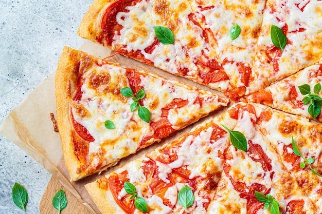 Klassische pizza margarita mit mozzarella, tomate und basilikum auf einem holzbrett. italienisches lebensmittelkonzept. Premium Fotos