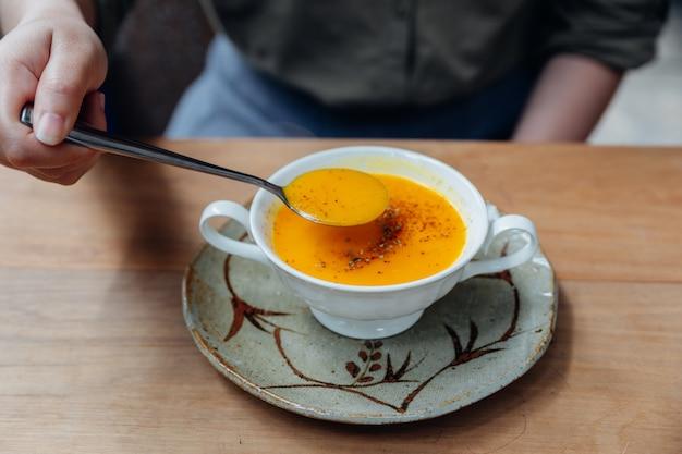 Klassische pürierte kürbissuppe mit pfeffer von hand übergießen.