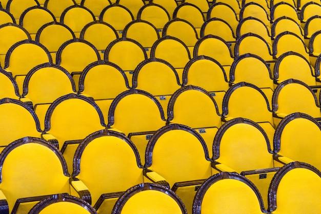 Klassische reihen von leeren gelben sitzen in einem kino oder in einem theater. halle ohne besucher. russischer palast der kultur. niemand kam zum konzert. die leute waren weg. ein schlechtes stück oder film. kopieren sie platz.