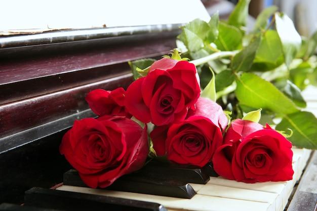 Klassische rote rosen auf romantischen valentinsgrüßen der klavierweinlese