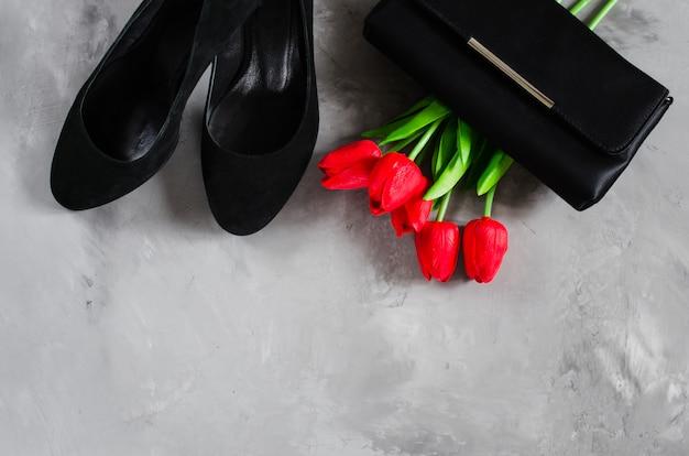 Klassische schwarze damenschuhe, kleine handtasche und rote tulpen.