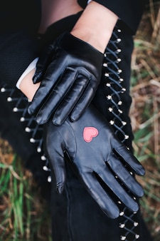 Klassische schwarze handschuhe mit einem herzen in seiner handfläche auf einer weiblichen hand.