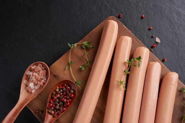 Klassische schweinefleischwürste mit gekochtem fleisch auf schneidebrett mit pfeffer und basilikum, petersilie, thymian und kirschtomaten. snack für kinder. schwarze oberfläche. würstchen mit gewürzen und kräutern, selektiver fokus.