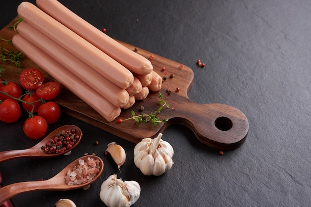Klassische schweinefleischwürste mit gekochtem fleisch auf schneidebrett mit pfeffer und basilikum, petersilie, thymian und kirschtomaten.