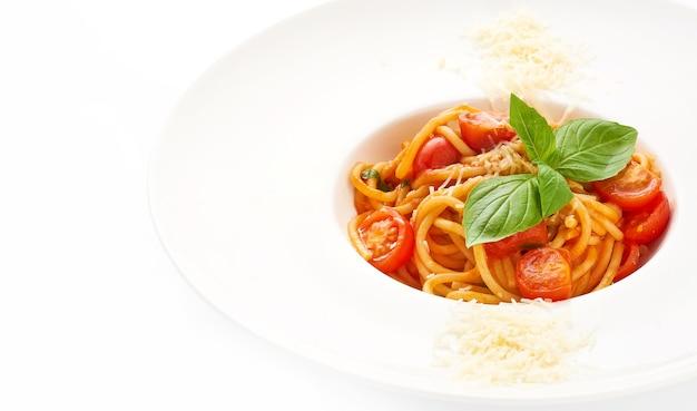 Klassische spaghetti mit kirschtomaten und parmesan, dekoriert mit basilikum auf weißem teller