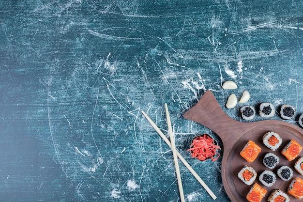 Klassische sushi-rollen auf holzbrett mit stäbchen.