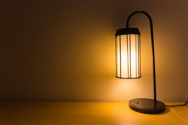 Klassische tischlampe auf hölzernem wand- und tabellenhintergrund