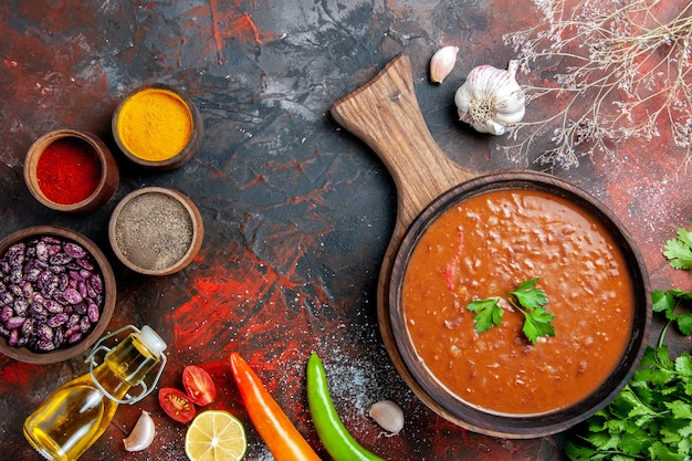 Klassische tomatensuppe gefallene ölflasche bohnen knoblauch und verschiedene gewürze auf schneidebrett