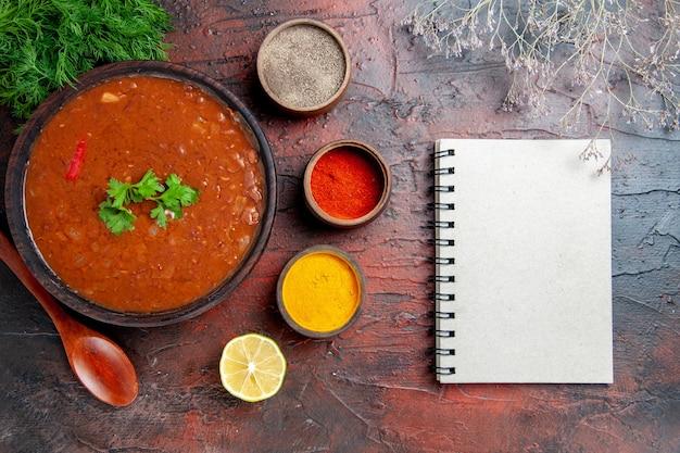 Klassische tomatensuppe in einer braunen schüssel verschiedene gewürze und notizbuch auf gemischter farbtabelle