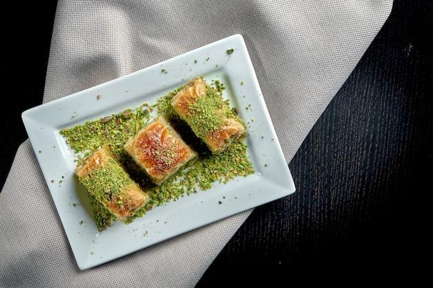 Klassische türkische süßigkeiten - baklava mit honig und pistazien aus blätterteig in einem weißen teller. nahaufnahme, selektiver fokus