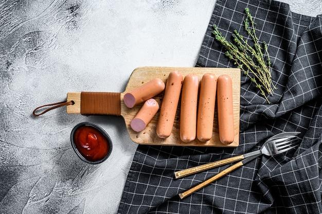 Klassische würste aus gekochtem schweinefleisch auf einem schneidebrett mit rosmarin und gewürzen.