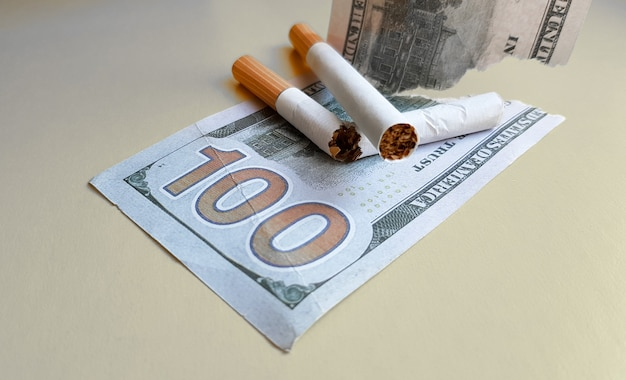 Klassische zigaretten stehen auf hundert-us-dollar-scheinen. zigaretten auf hundert-dollar-schein auf gelbem grund.