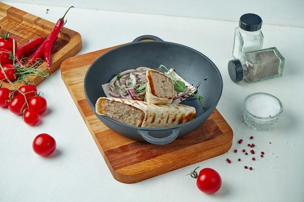 Klassischer arabischer hühnchen-lula-kebab in fladenbrot mit zwiebelgarnitur in einer dekorativen pfanne. appetitliches fleisch auf dem grill.