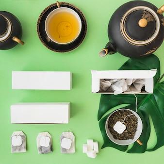 Klassischer asiatischer teesatz mit kräuterteebeutel auf grünem hintergrund