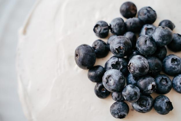 Klassischer blaubeerkäsekuchen-kuchen mit sahne auf einem weißen hölzernen küchentisch. horizontaler hintergrund der süßen konditorei.