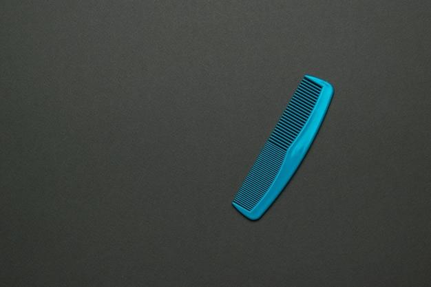Klassischer blauer kunststoffkamm auf schwarzem hintergrund. flach liegen. Premium Fotos
