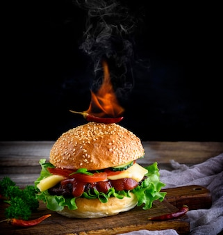 Klassischer burger mit frikadelle, käse und gemüse auf einem brötchen mit sesam ist eine brennende rote chilischote