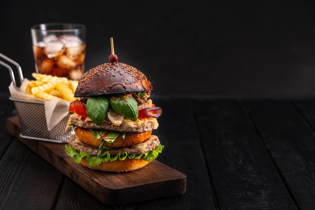 Klassischer burger mit pommes und coca cola auf einem dunklen hintergrund