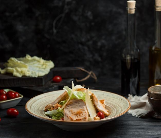 Klassischer caesar-salat mit fischfilet und parmesan auf der oberseite